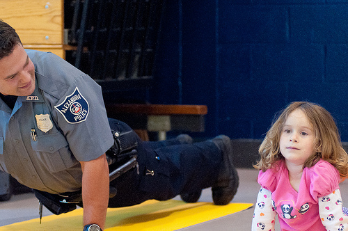 child and police officer doing yoga