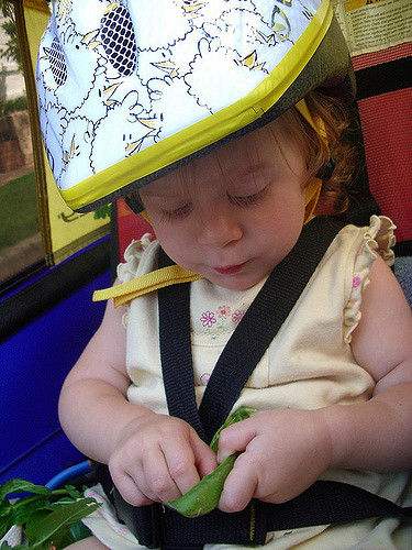 child in bike carrier eating peas