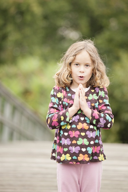 Child on bridge in mountain pose